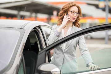 Beautiful red hair businesswoman standing in front of the car and talking on phone.