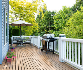 Home deck and patio with outdoor furniture and BBQ cooker with bottled beer