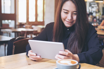 A beautiful Asian woman with smiley face using tablet in modern cafe