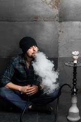 Young handsome bearded man smoking hookah