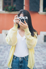 young pretty woman taking picture with old camera