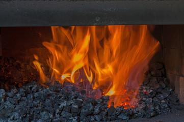 Orange flames blaze inside the dark coal forge