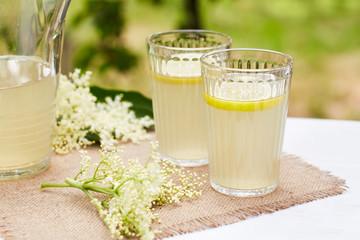 Two glasses of elderflower lemonade with fresh lemon