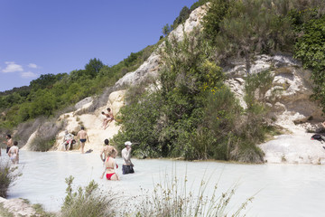 Bathing in the free area of Bagno Vignoni in Tuscany, Italy, free accessible hot springs puddle trough vegetation