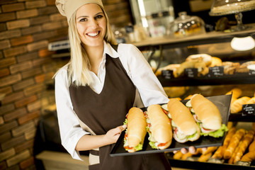 Beautiful female bakery posing with various types of sandwiches in the baker shop