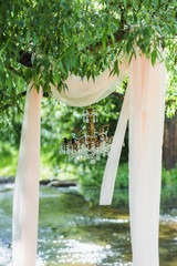 Beautiful luxury decor for outside wedding celebration. Festive photobooth. Christal chandelier without bulbs hanging in green summer park or wood. Arch decorated with draped fabric. Vertical photo.