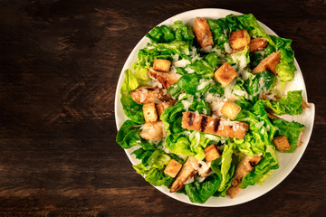 Chicken Caesar salad on rustic background with copyspace