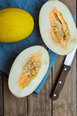 Ripe organic yellow melons, halved and whole on dark plank wood background, pulp and seeds, blue linen napkin, knife, top view, rural style
