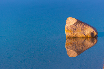 Lake surface with symmetrical reflection of stone in the water. Sunset light.