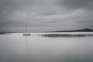 Morski krajobraz z zacumowanym jachtem przy spokojnej zatoce. Gładka powierzchnia wody przy długiej ekspozycji. Dramatyczne chmury nad jesień jeziorem. Stroiki w wodzie o gładkim odbiciu jak histogram fali dźwiękowej. - 158773693