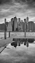 Manhattan skyline reflected in a puddle, Brooklyn Borough, New York City, USA.
