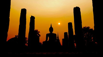 Sunset silhouettes of the Wat Mahathat Temple in Sukhothai Historical Park, Thailand, a UNESCO Heritage Site.