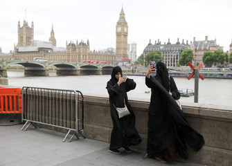 Two women wearing Muslim dress use their smartphones opposite the Houses of Parliament in London