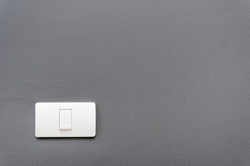 Light switch on gray concrete wall background.