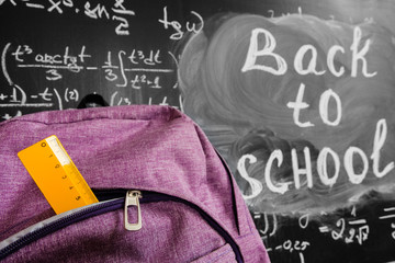 """Back to school background with purple school bag with yellow ruler and the title """"Back to school"""" and math formulas written by white chalk on the black school chalkboard"""
