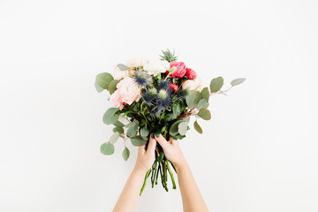 Beautiful flowers bouquet in girls hands: bombastic roses, blue eringium, eucalyptus, isolated on white background. Flat lay, top view. Floral composition Fototapete