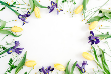 Round frame wreath with yellow tulips, purple iris and chamomile flowers on white background. Flat lay, top view. Floral background