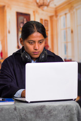 Close up portrait of indigenous young latin man using laptop