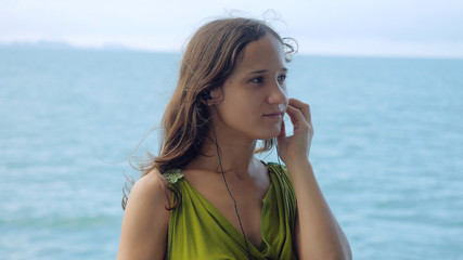 Beautiful dreamy young woman listening to music on headphones on the sailing ship