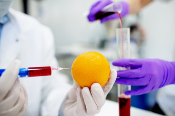 Doctor holding orange in his hands. Close up of injecting chemical substances into orange. GMO experiments.