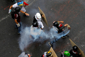 A demonstrator prepares to throw a tear gas canister during riots at a rally against Venezuelan President Nicolas Maduro's government in Caracas,