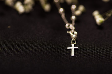 Rosary beads with blurred white small flowers, black background