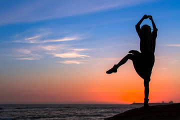 Silhouette of a fun young woman on the sea coast during twilight.