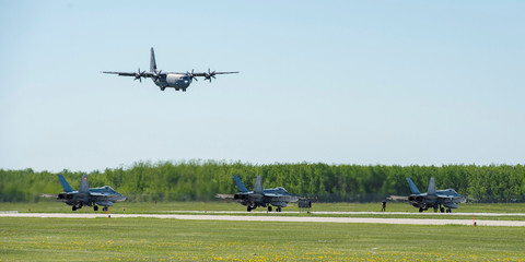 A Royal Canadian Air Force CC-130 Hercules starts its descent as three CF-188 Hornets sit on the tarmac during Exercise MAPLE FLAG 50 at 4 Wing Cold Lake