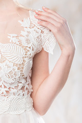 fashionable gown, beautiful wedding model, bride style and concept - closeup on white graceful wedding dress of pretty young woman posing in studio, subtle embroidery and the lightness of the fabric.