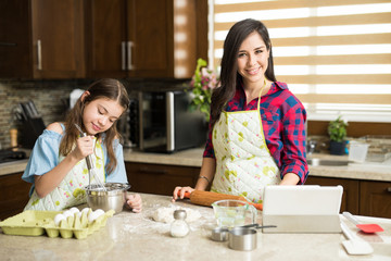 Latin mother cooking with her daughter