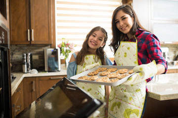 Girl and her mom baking cookies together