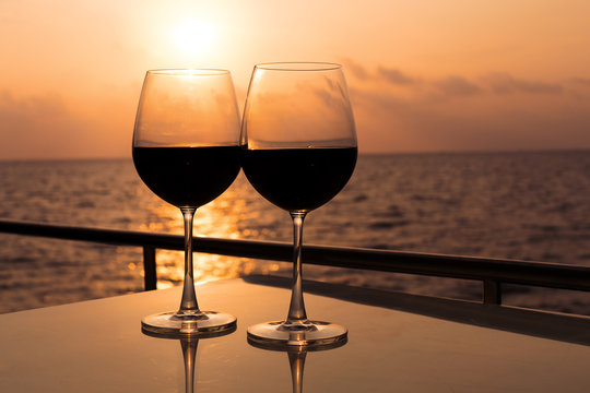 Glasses, red wine and tropical sunset with sea background, nobody.