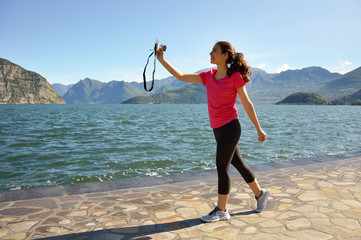Smiling fitness girl take selfie with mirrorless camera with beautiful lake landscape on the background