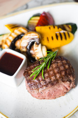 Close-up of pork steak with garnish, grilled vegetables, champignon mushrooms, pepper, zucchini, with sauce, decorated with rosemary, beautiful trendy serve, healthy tasty food, restaurant