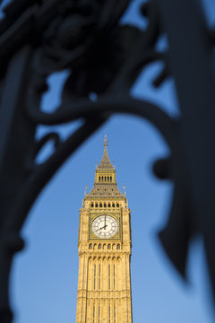 Big Ben, also known as Queen Elizabeth Tower, standing in bright blue sky behind the dark defocused silhouette of the gothic iron gates of Westminster Palace in London, United Kingdom