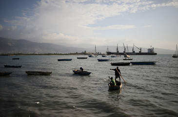 A man anchors a boat next to the shore in Port-au-Prince, Haiti