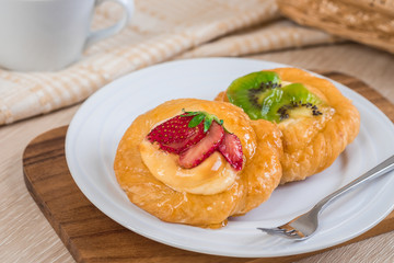 Danish pastry with fruit on plate and coffee cup
