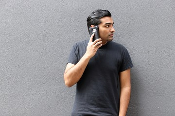 Handsome man wearing black shirt standing against gray wall looking to the side with serious face