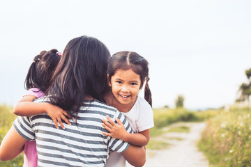 happy asian little girls hugging mother and having fun to play with mother in vintage color tone
