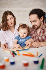 Portrait of family spending time with cute little daughter, reading stories and painting together