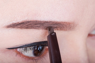 woman using pencil makeup eyebrow