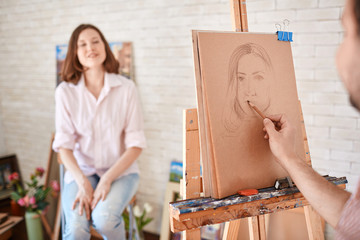 Portrait of artist sketching portrait of young woman sitting in front of him in art studio