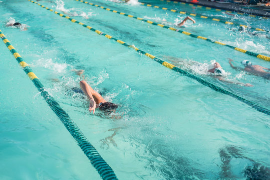 Close-up action shot of teen boy swimming front crawl stroke style in the blue water outdoor race pool. Focus on arm and water splash, some motion blurs. Summer, swimming race and competition concept.
