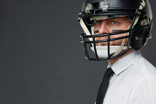 Closeup portrait of confident middle aged businessman with army paint on his face wearing helmet and looking at camera away against grey background