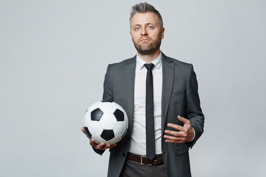 Waist up studio portrait of middle aged man with grey hair holding soccer ball and looking at camera