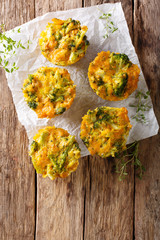 Broccoli Muffins with cheddar cheese and thyme close-up on the table. vertical top view