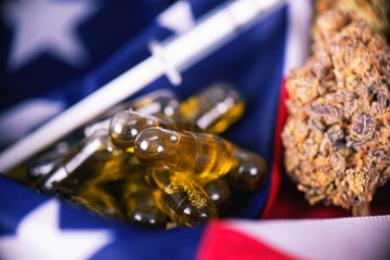 Detail of cannabis CBD oil capsules and bud in front of american flag