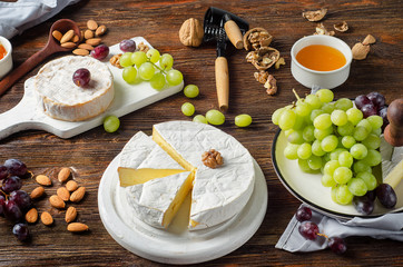 Cheese Brie with grapes and nuts on a wooden board