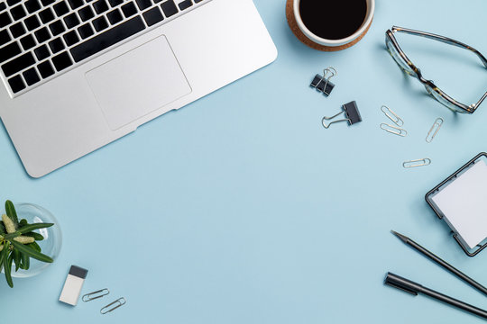 Top view workspace mockup on blue background with notebook, pen, coffee, clips and accessories.