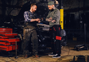 Two bearded  mechanics inspecting car's engine parts.